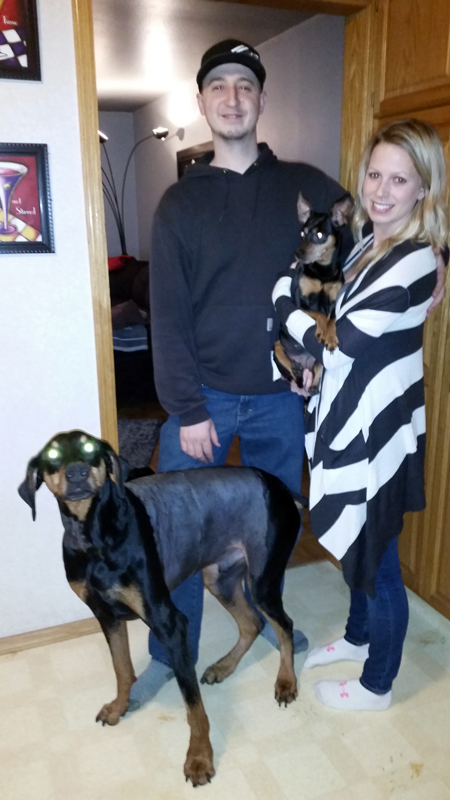 Doberman Pinscher, deuce with owners and a puppy